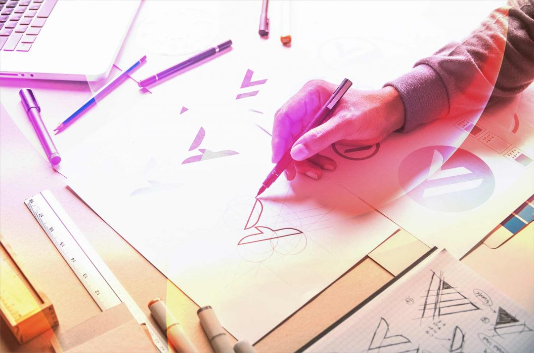artist at desk with pen in hand drawing logo